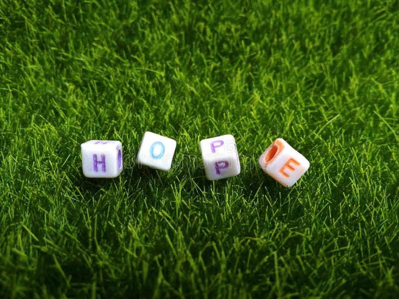 Illustration for hope, alphabet plastic bead at artificial green grass royalty free stock images