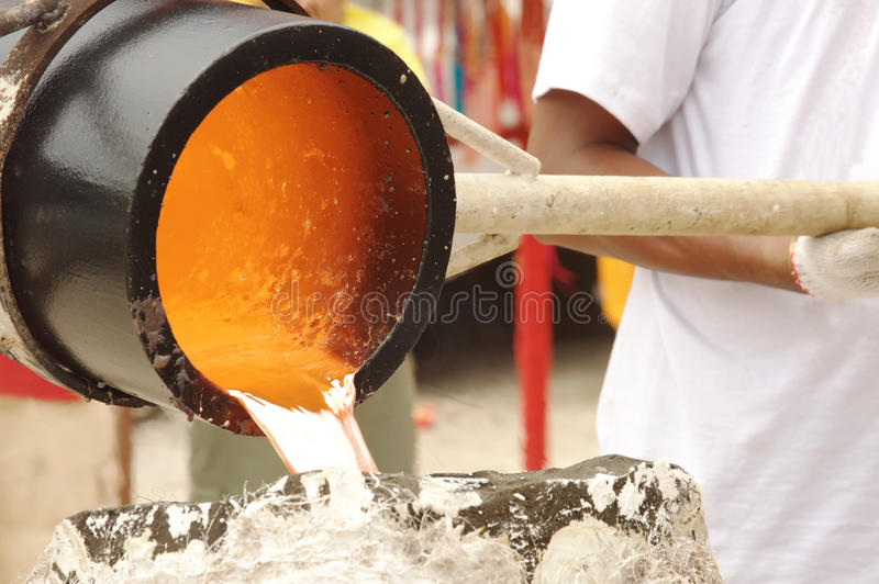 Illustration of molten metal being poured from a foundry crucible statue stock photography