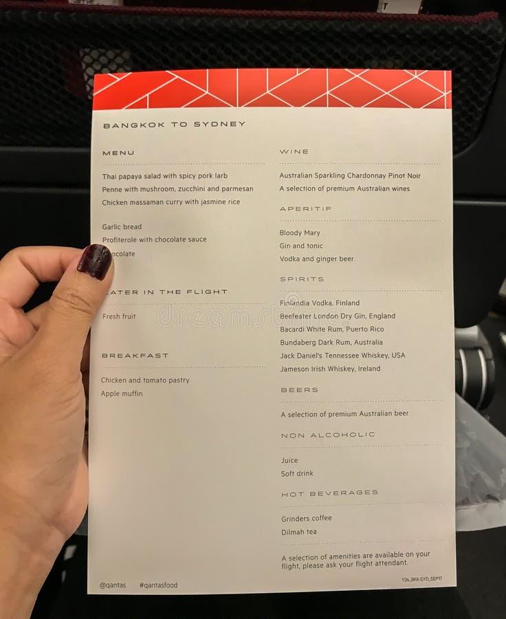 Illustrative editorial brochure menu on economy class of Qantas Airlines. Illustrative editorial brochure menu in woman hand on economy class of Qantas Airlines royalty free stock photos