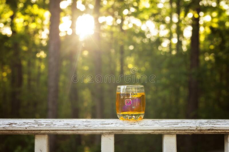 Illustrative editorial image of a shot of whiskey on a porch rail. Illustrative editorial image of a shot of whiskey in a porch railing with sun rays coming stock photo