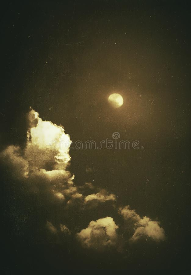 A beautiful glowing moon and clouds in a dark sky. An illustrative image of a beautiful glowing moon and clouds in a dark sky stock illustration