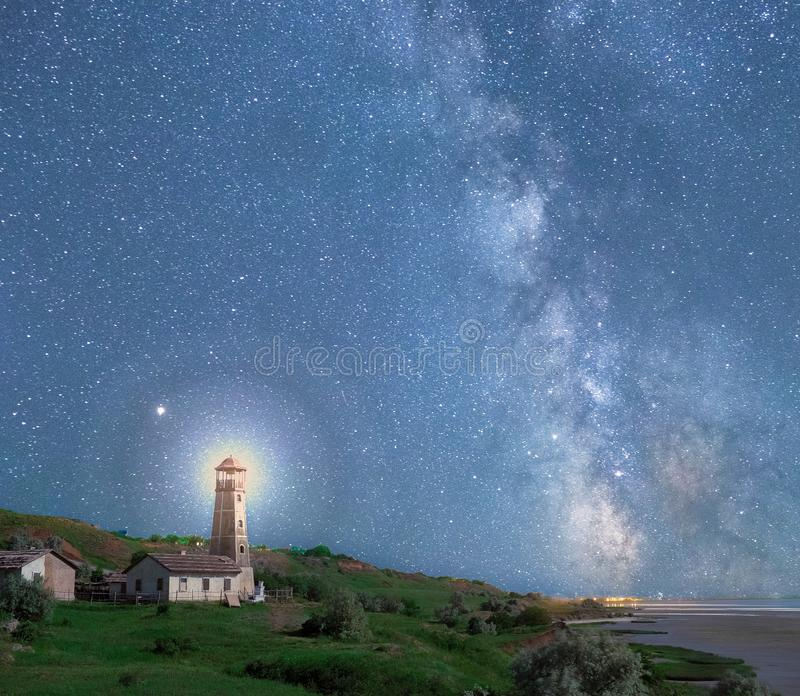 An illustrative image of a nautical beacon on the shore overgrown with grass at night under the sky. With a milky way royalty free stock photos