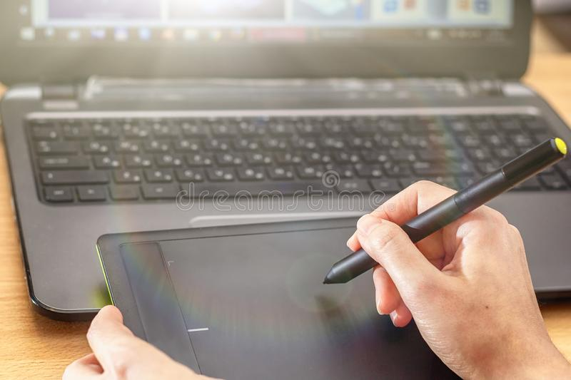 Illustrator using a graphics tablet. Woman`s retoucher`s hands using laptop and drawing tablet.  royalty free stock photos