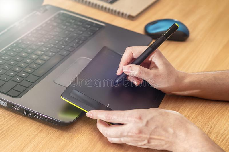 Illustrator using a graphics tablet. Woman`s retoucher`s hands using laptop and drawing tablet.  stock image