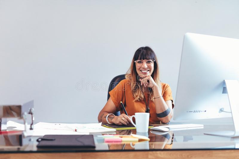 Illustrator working on her drawings at office. Smiling creative artist sitting at her desk in office making a sketch on a digital writing pad. Illustrator stock photo