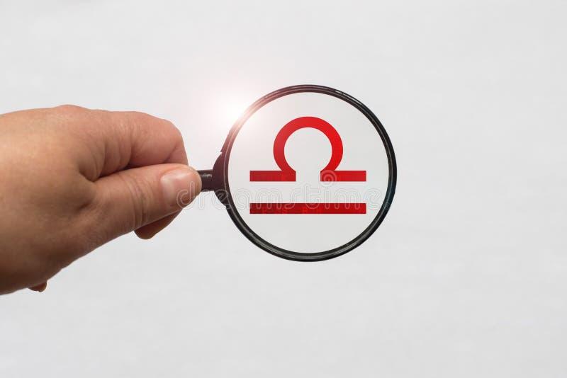 Illustrazione di una messa a fuoco della lente d'ingrandimento sul segno rosso dello zodiaco della Bilancia immagine stock libera da diritti