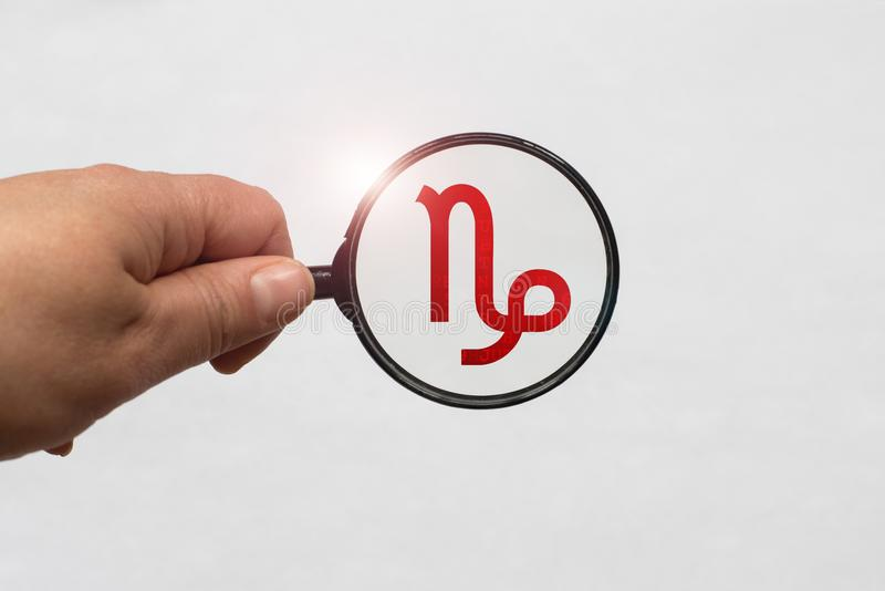 Illustrazione di una messa a fuoco della lente d'ingrandimento sul segno rosso dello zodiaco di capricorno immagine stock