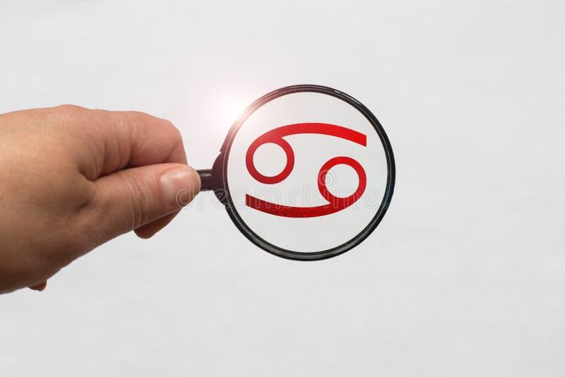 Illustrazione di una messa a fuoco della lente d'ingrandimento sul segno rosso dello zodiaco del Cancro immagini stock