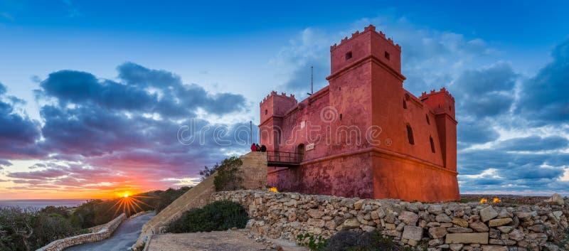 IlMellieha,马耳他-观看日落的游人在与美丽的天空的圣阿佳莎` s红色塔 库存图片