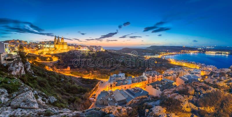 IlMellieha,马耳他- Mellieha镇美好的全景地平线视图在日落以后的与巴黎教会和Mellieha靠岸 库存图片