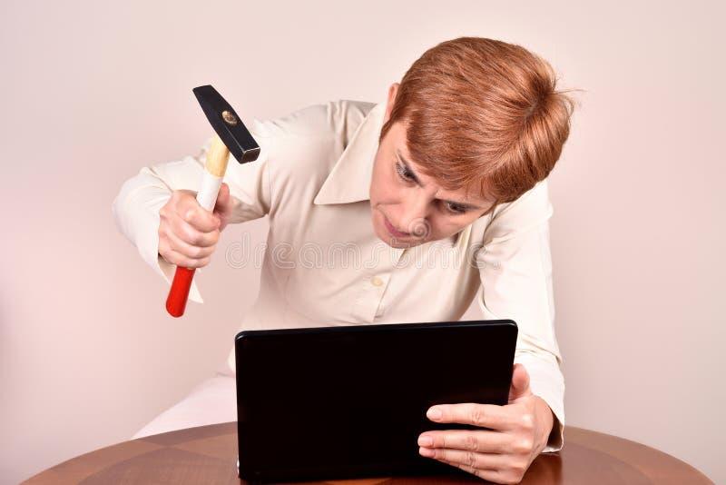 Ilsken affärskvinna med en hammare och en bärbar dator royaltyfria bilder