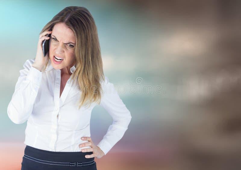 Ilsken affärskvinna på telefonen mot oskarp bakgrund för blå brunt royaltyfria foton