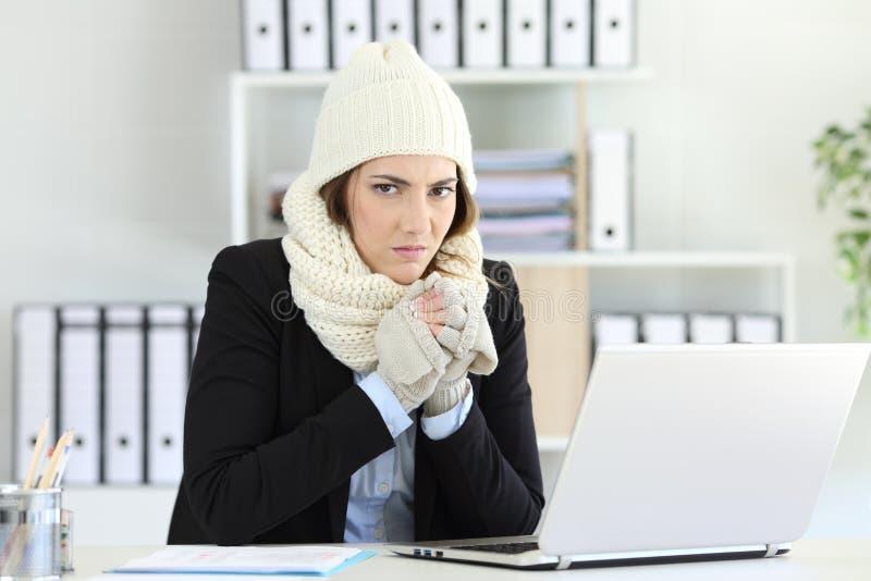 Ilsken affärskvinna som har förkylning på kontoret arkivbild