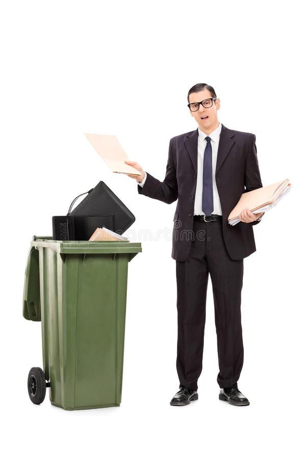 Ilsken affärsman som kastar hans material i avfallet arkivbild