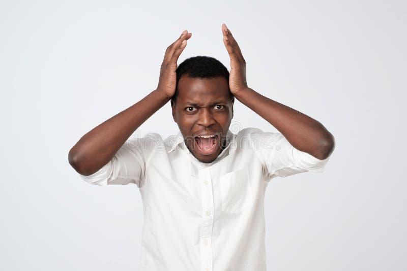 ilsken afrikansk man som rymmer händer på hans framsida och ropa som isoleras över den gråa väggen arkivbilder