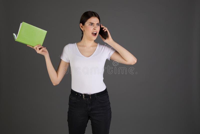 Ilsken aggressiv brunettaffärskvinna i den vita t-skjortan royaltyfri foto