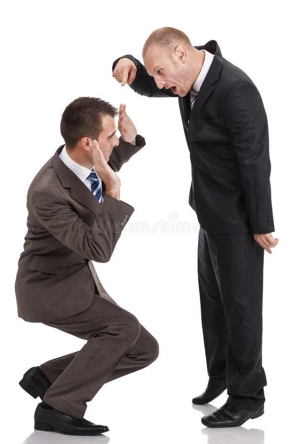 Ilsken arbetsgivare som ropar och pekar på huka sig ned anställd arkivbilder