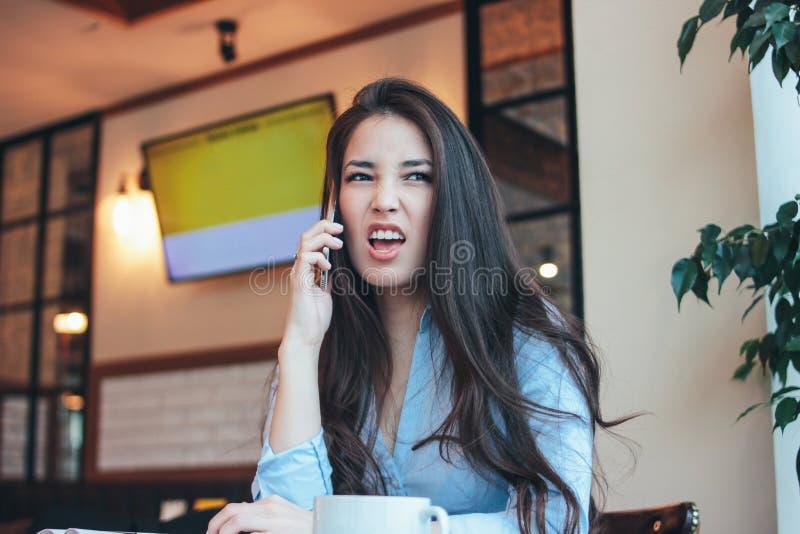 Ilsken asiatisk flicka för härlig charmig brunett som talar och argumenterar med någon på telefonen arkivbild