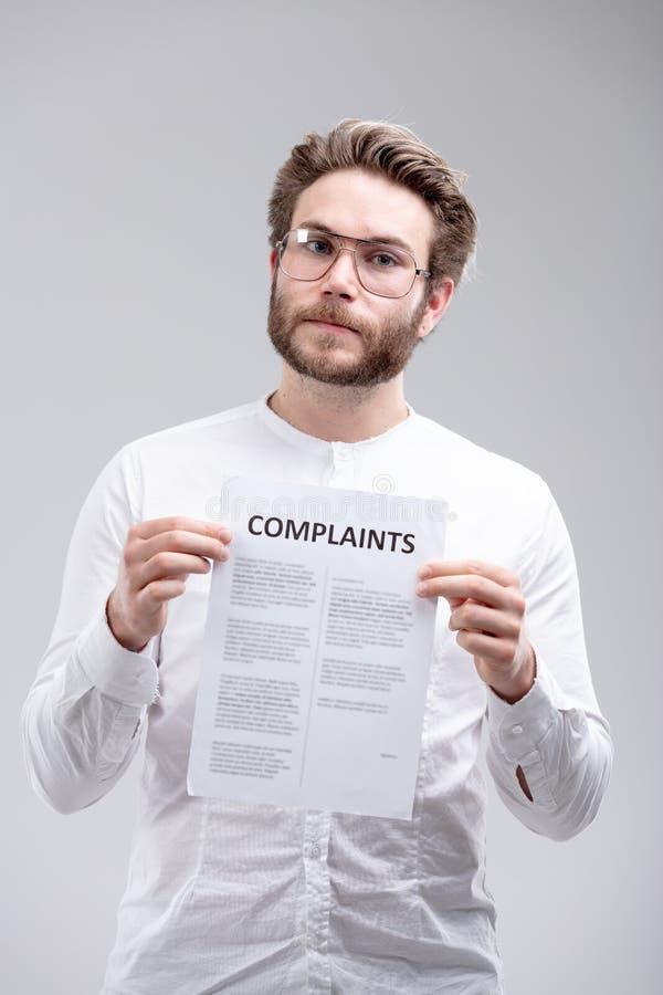 Ilsken beslutsam man som rymmer en lista av klagomål royaltyfri foto