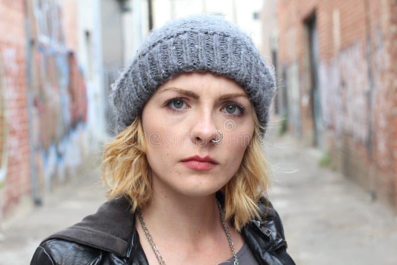 Ilsken blond kvinna för stående på stads- kall bakgrund arkivbilder