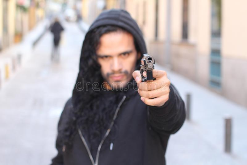 Ilsken brottsling som utomhus rymmer ett vapen arkivfoto