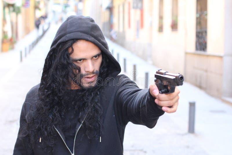 Ilsken brottsling som utomhus rymmer ett vapen fotografering för bildbyråer