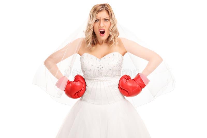 Ilsken brud i en bröllopsklänning och boxninghandskar arkivfoto