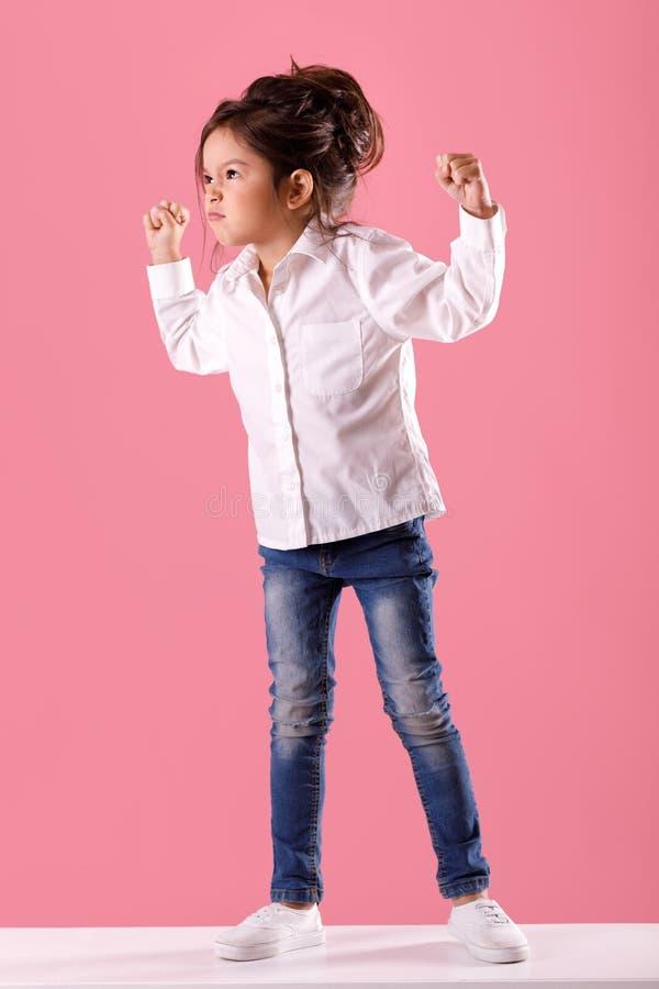 Ilsken flicka för litet barn i den vita skjortan med frisyren royaltyfria foton