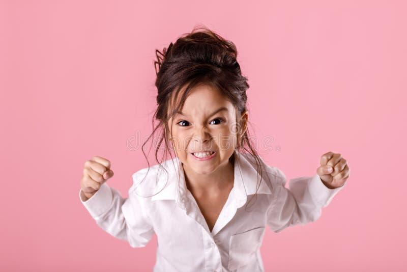 Ilsken flicka för litet barn i den vita skjortan med frisyren royaltyfri fotografi