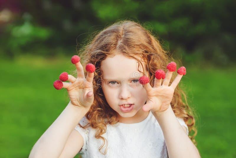 Ilsken flicka med hallon på hennes fingrar royaltyfri foto