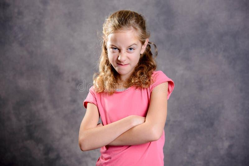 Ilsken flicka med skjortan för blont hår och rosa färg royaltyfria bilder