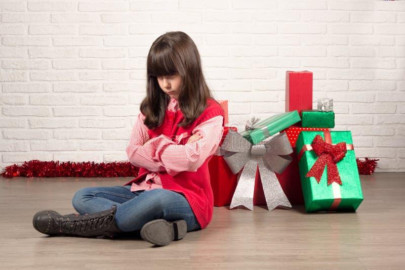 Ilsken flicka på jul med gåvaaskar fotografering för bildbyråer
