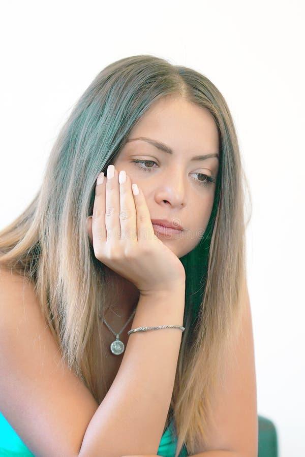 Ilsken flicka som sitter på soffan arkivbild