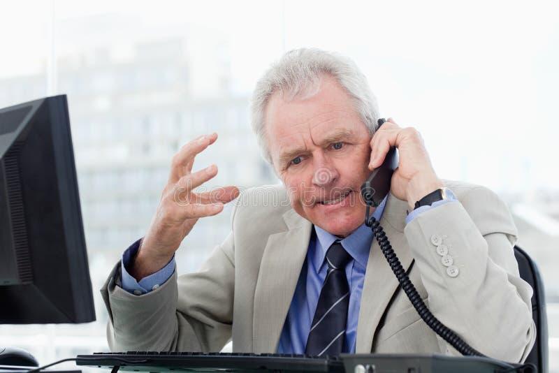 Ilsken hög chef på telefonen royaltyfri bild