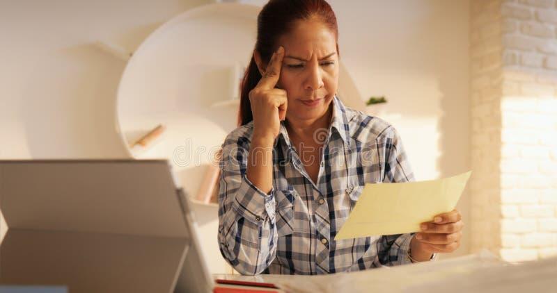 Ilsken hög kvinna som betalar räkningar och sparar federal skattretur arkivbild