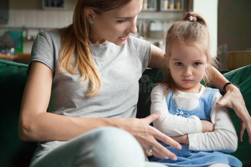 Ilsken kränkt liten flicka som ignorerar moderord, rådgivning royaltyfri fotografi