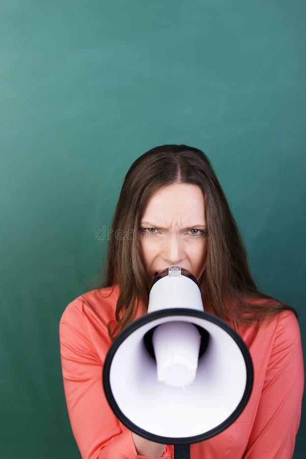 Ilsken kvinna med en megafon arkivbilder