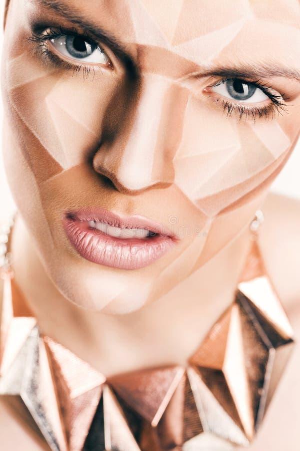 Ilsken kvinna med geometrisk bodyart på framsida royaltyfri fotografi