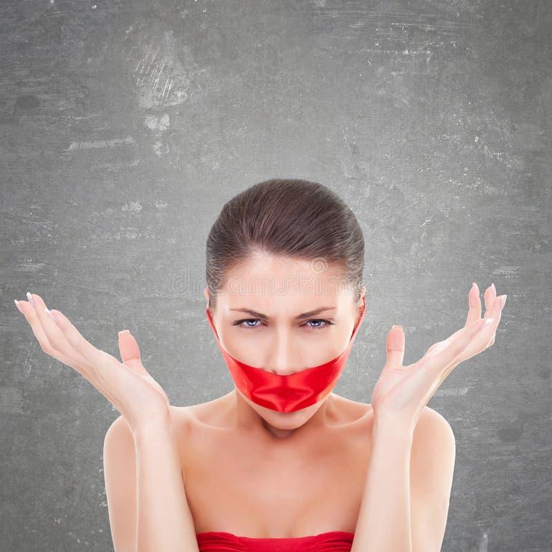 Ilsken kvinna med munnen som täckas med ett rött band royaltyfri bild