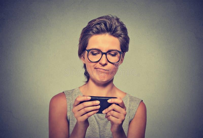 Ilsken kvinna med olyckliga exponeringsglas, förargat vid något på att smsa för mobiltelefon arkivfoton