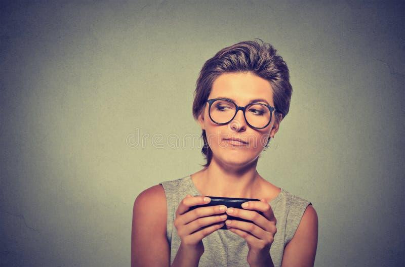 Ilsken kvinna med olyckliga exponeringsglas, förargat vid något på att smsa för mobiltelefon royaltyfri bild