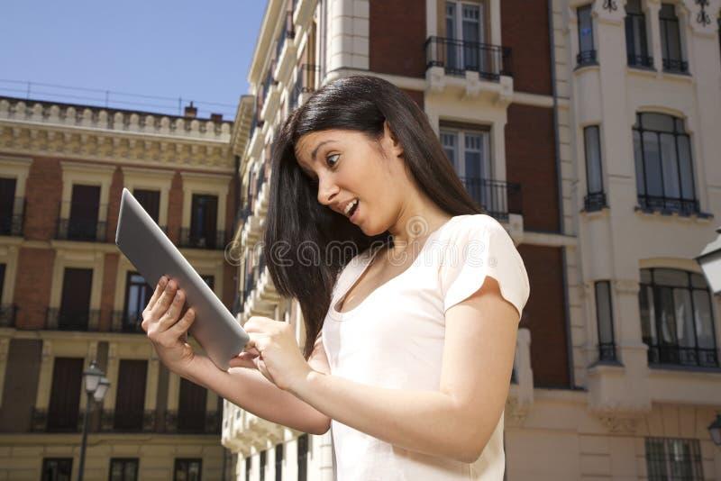 Ilsken kvinna som håller ögonen på den digitala minnestavlan royaltyfri bild