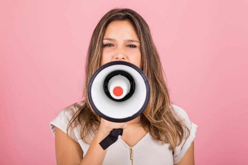 Ilsken kvinna som protesterar, medan genom att använda megafonen royaltyfri bild