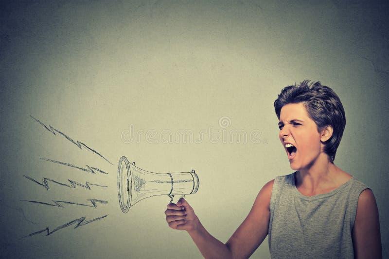 Ilsken kvinna som rymmer att skrika i megafon fotografering för bildbyråer