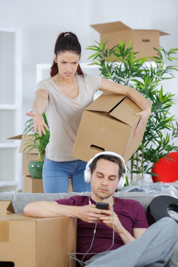 Ilsken kvinna som skriker på den lata pojkvännen under att flytta sig arkivfoton