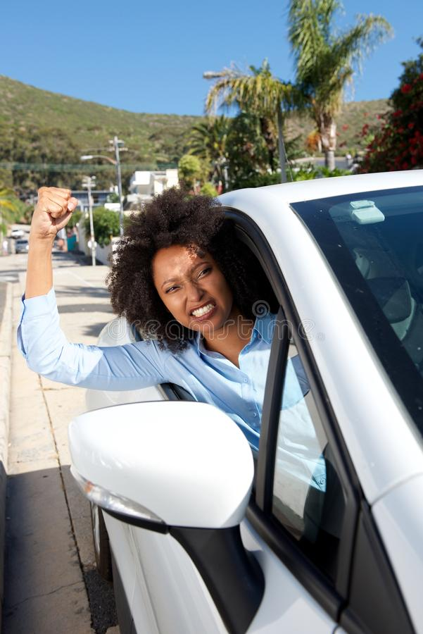 Ilsken kvinnlig bilchaufför som visar hennes näve, medan köra arkivfoton