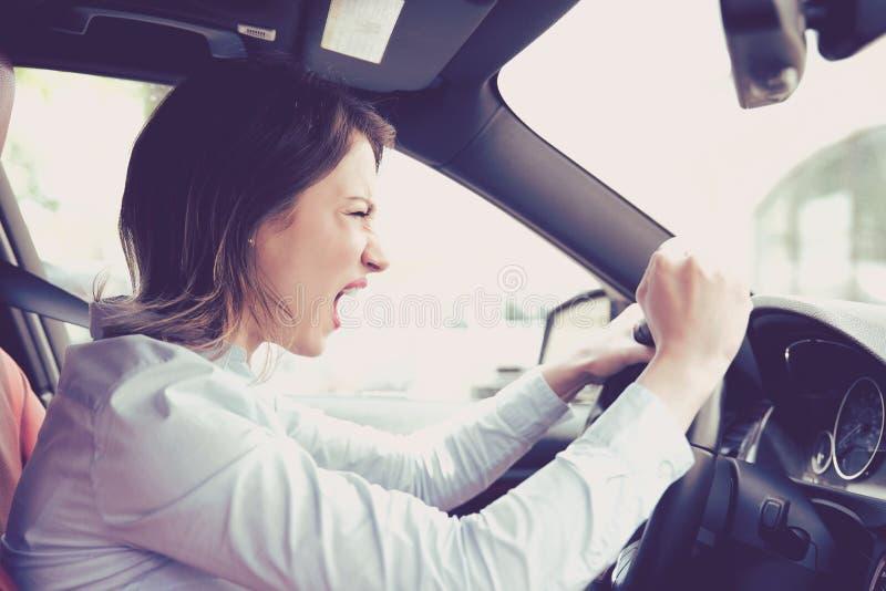 Ilsken kvinnlig chaufför för sidoprofil som skriker, medan köra hennes bil royaltyfria bilder