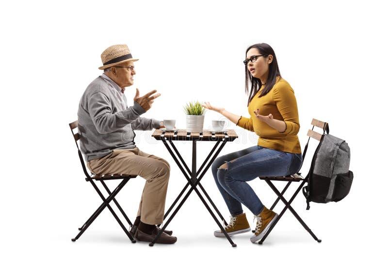 Ilsken kvinnlig student i ett kafé som sitter på en tabell och argumenterar med en äldre man arkivbild