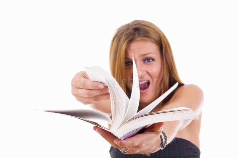 Ilsken kvinnlig student som bläddrar en bok royaltyfri foto