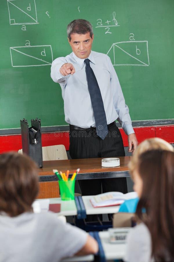 Ilsken lärare Pointing At Schoolboy i klassrum royaltyfria bilder